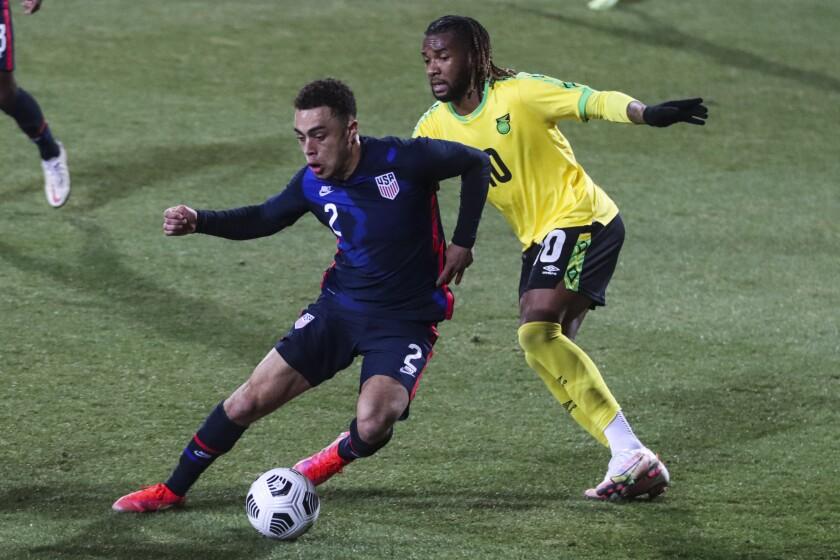 El lateral estadounidense Sergiño Dest pugna por el balón