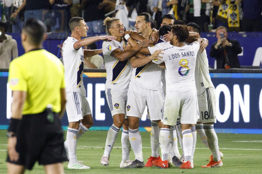 Zlatan Ibrahimovic, center, is swarmed by teammates after scoring one of his three goals against LAFC on Friday night.