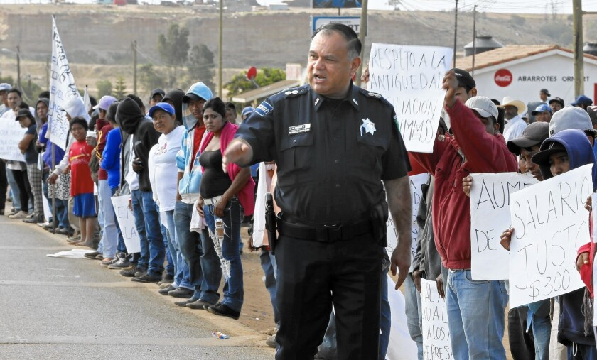 A Mexican police officer orders striking farmworkers to stay off the Transpeninsular Highway.