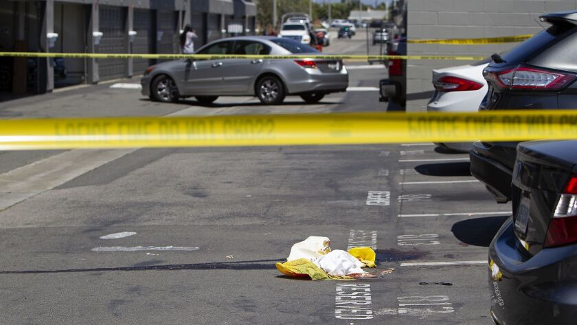Blood stains the pavement in a parking lot where a person was shot Monday morning at the Breakwater
