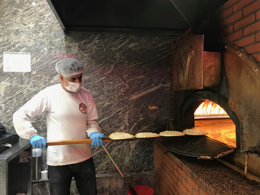 Kamal, one of Barbar's remaining bakers, slides flatbread into the brick oven while making manousheh, a kind of Lebanese pizza.