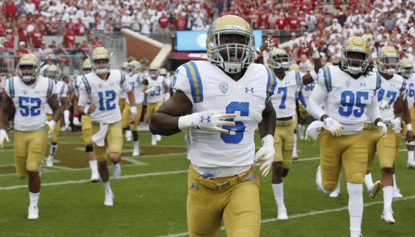 UCLA runs onto the field before an NCAA college football game against Oklahoma in Norman, Okla., Sat