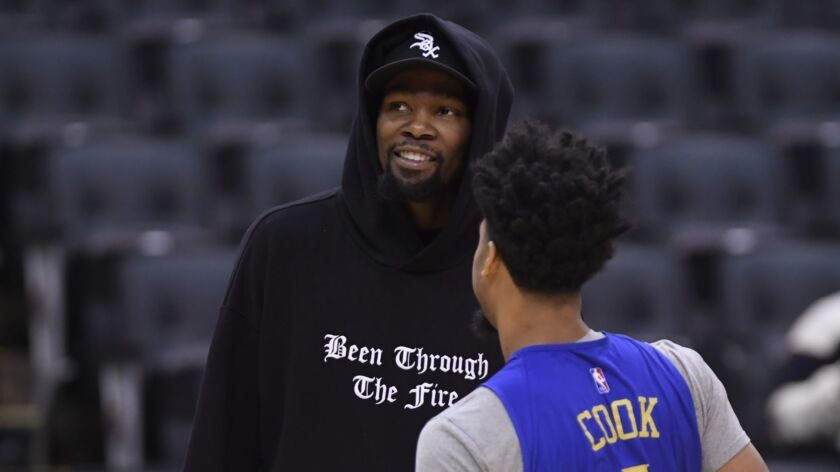 Golden State Warriors Kevin Durant, left, talks with teammate Stephen Curry during basketball practi