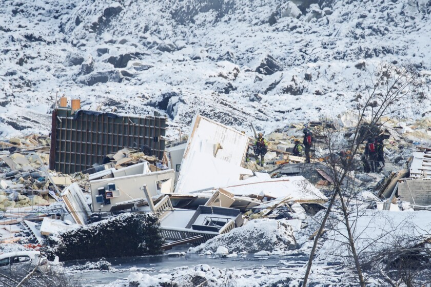 Rescue workers stand on and around home debris and snow at the scene of a deadly landslide.