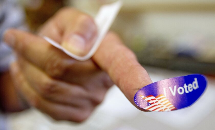 """Fred Pascasio shows his """"I voted"""" sticker after voting at Hawthorne Elementary School in Clairemont on Tuesday."""