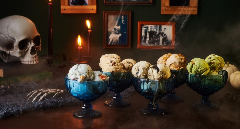 A fake skull and skeleton hand sit next to bowls of ice cream.