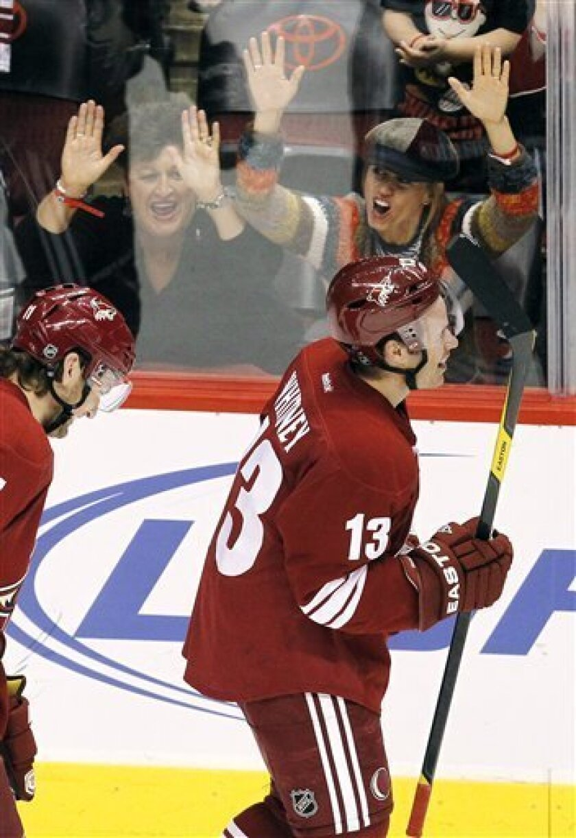Phoenix Coyotes' Ray Whitney (13) smiles as he skates past cheering fans after recording his 1,000th career point on an assist against the Anaheim Ducks during the second period in an NHL hockey game, Saturday, March 31, 2012, in Glendale, Ariz. (AP Photo/Ross D. Franklin)