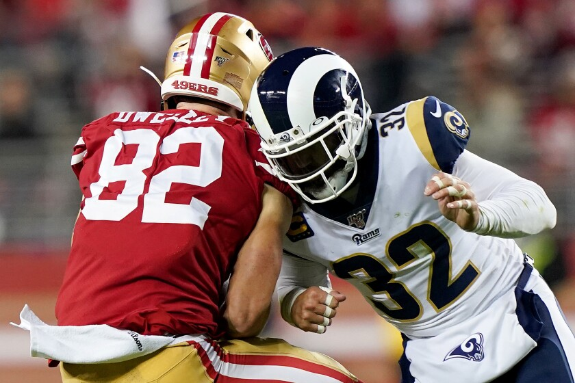Rams safety Eric Weddle puts a hit on San Francisco 49ers tight end Ross Dwelley after he makes a first-down catch Saturday.