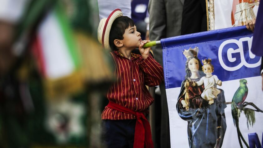 Jonah Oliviero Trabanino, 5, plays with a banner that represents the Virgin of Guatemala.