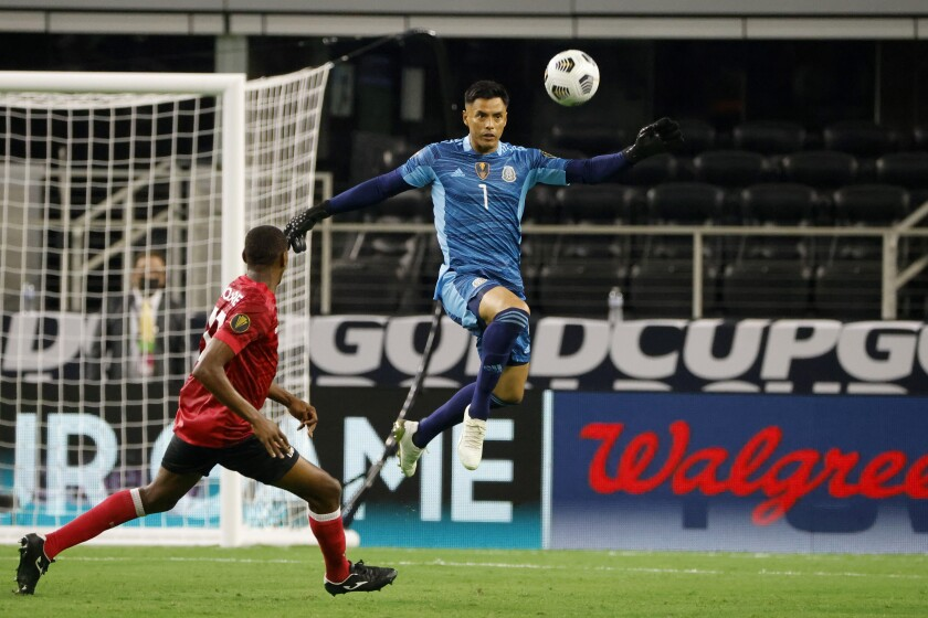 Mexico goalkeeper Alfredo Talavera (1) clears the ball away from Trinidad and Tobago midfielder Reon Moore during a CONCACAF Gold Cup Group A soccer match in Arlington, Texas, Saturday, July 10, 2021. (AP Photo/Michael Ainsworth)