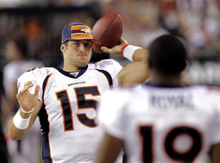 Denver Broncos quarterback Tim Tebow (15) warms up on the sidelines during the first half of the Broncos' NFL preseason football game against the Arizona Cardinals, Thursday, Sept. 1, 2011, in Glendale, Ariz. (AP Photo/Paul Connors)