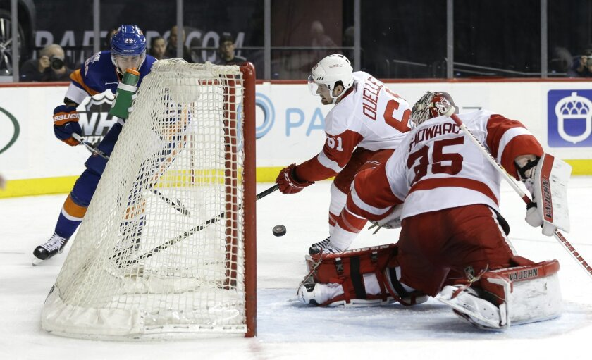 New York Islanders' Brock Nelson, left, scores  past Detroit Red Wings goalie Jimmy Howard, right, and Xavier Ouellet during the second period of an NHL hockey game, Monday, Feb. 15, 2016, in New York. (AP Photo/Seth Wenig)