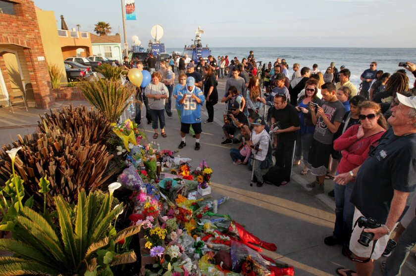 A crowd forms at dusk in front of Junior Seau's house on The Strand.