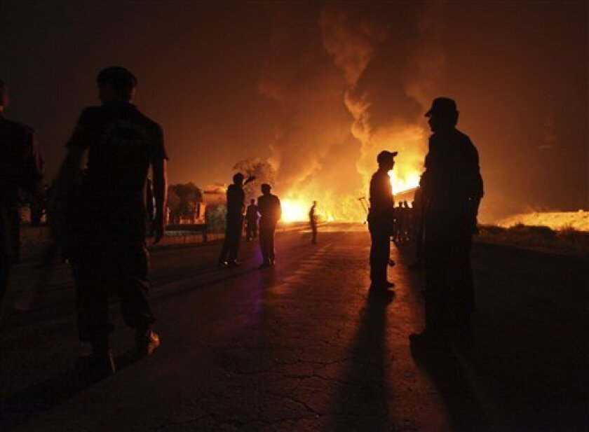Pakistani soldiers stand near burning NATO oil tanker allegedly attacked by militants in Nowshera near Peshawar, Pakistan on Wednesday, Oct. 6, 2010. Gunmen in northwest Pakistan torched a dozen tankers carrying fuel to NATO troops police said, the latest strike against supply convoys heading for Afghanistan since Pakistan shut a key border crossing last week. (AP Photo/Mohammad Sajjad)