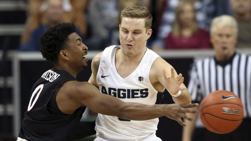 San Diego State's Devin Watson (0) defends as Utah State's Sam Merrill drives during the first half of Mountain West men's tournament championship game Saturday in Las Vegas.