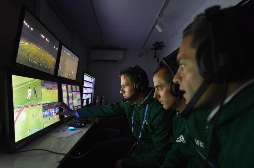 Un árbitro y dos asistentes de vídeo siguen el juego en sus monitores durante el partido del Mundial de Clubes de Japón 2016 entre el Kashima Antlers y el Auckland City en el estadio Yokohama de Japón.