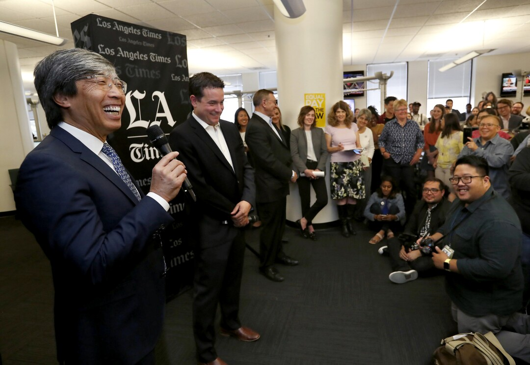 Dr. Patrick Soon-Shiong smiles as he speaks into a microphone in the Los Angeles Times newsroom