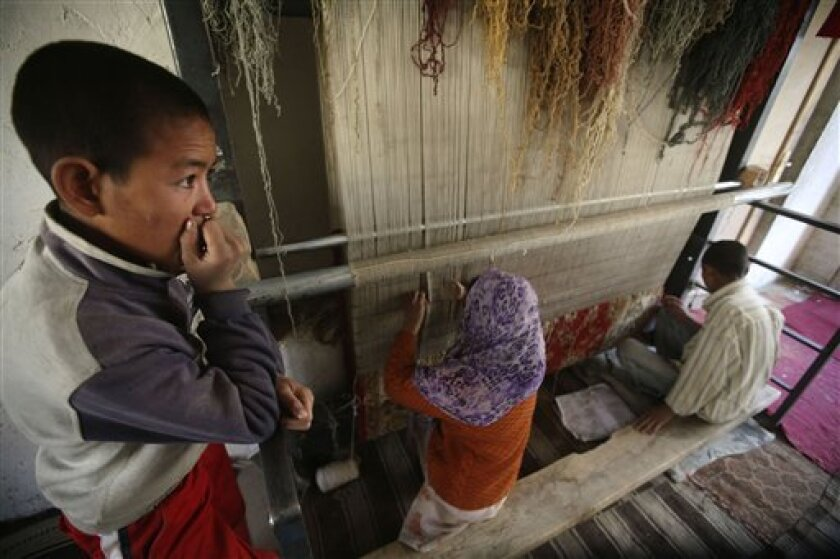 Khaled Dad, a son of Nasir Ali, a 50-year-old municipal worker killed in a suicide bomb attack, looks on as his brother and sister weave carpets in their home in Kabul, Afghanistan, Tuesday, Dec. 2, 2008. (AP Photo/Rafiq Maqbool)