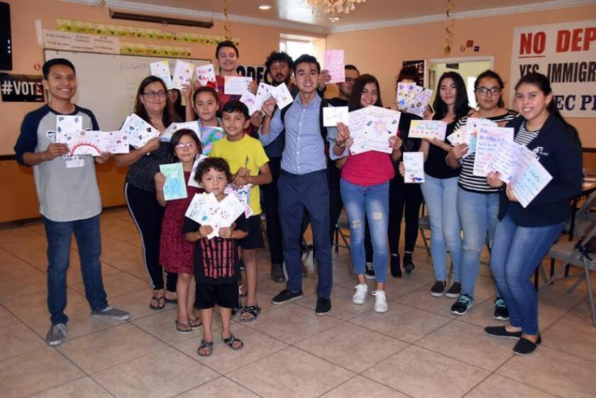 Jóvenes que en su momento llegaron como indocumentados a Estados Unidos posan con las cartas que escribieron a los nuevos niños albergados en los centros de detención del Servicio de Inmigración y Aduanas (ICE), el 19 de julio de 2018, en la sede del centro jurídico Formación para el Desarrollo Ocupacional de las Comunidades Educativas (TODEC) en Perris, California (Estados Unidos). EFE/Archivo