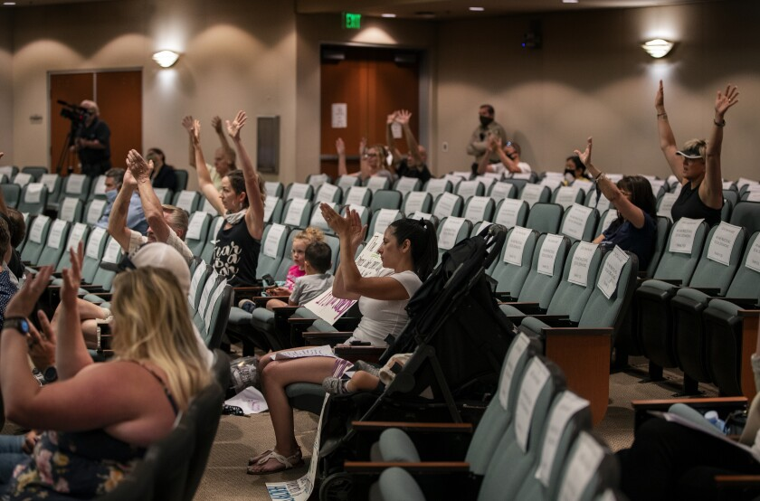 People cheer rescinding of health orders at a Riverside County supervisors meeting.
