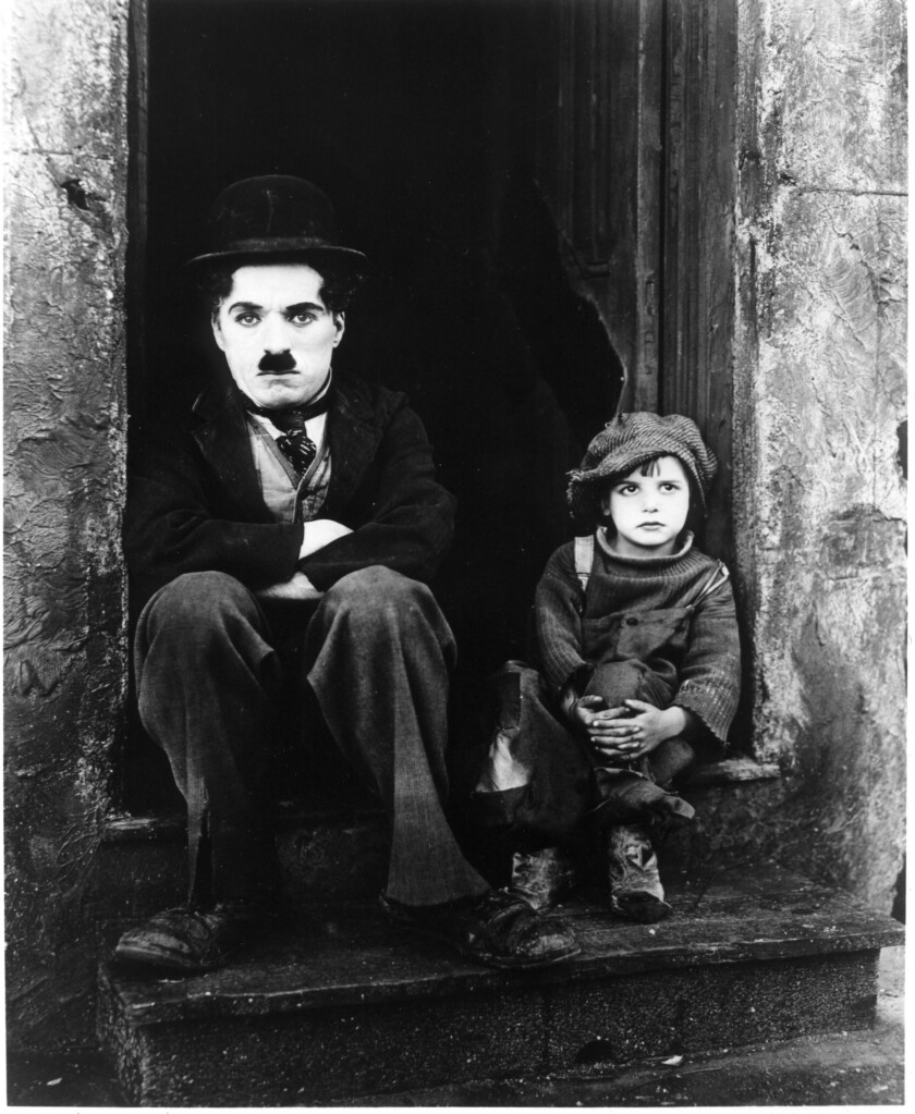 A black-and-white photo of a man and a child sitting on a stoop
