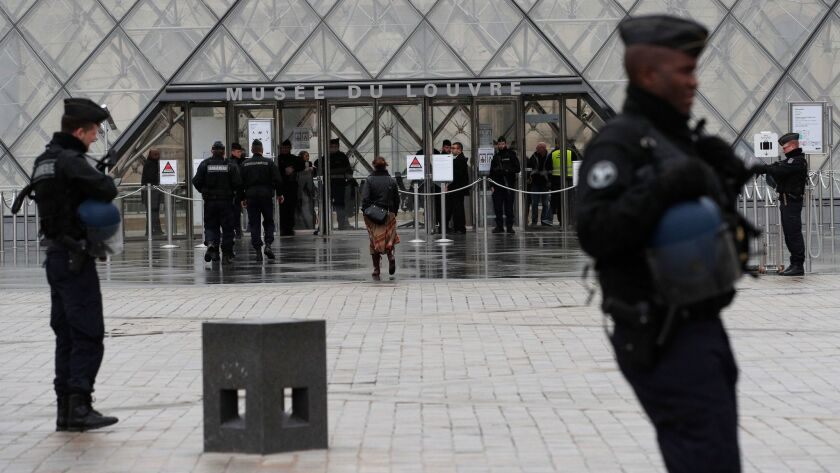 Armed police officers patrol in the courtyard of the Louvre Museum.