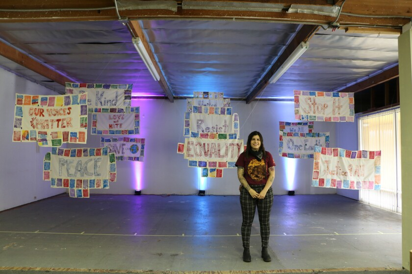 """Artist Jennifer Frost Moreno poses with banners created by students for Words Alive's """"Novel Ideas"""" virtual exhibit."""