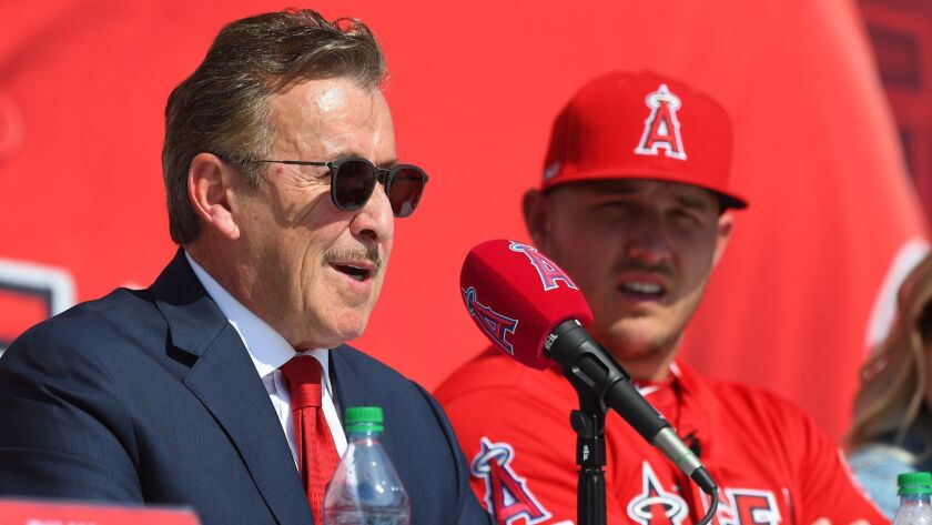 Mike Trout of the Angels looks on as owner Arte Moreno talks during Sunday's press conference at Angel Stadium.
