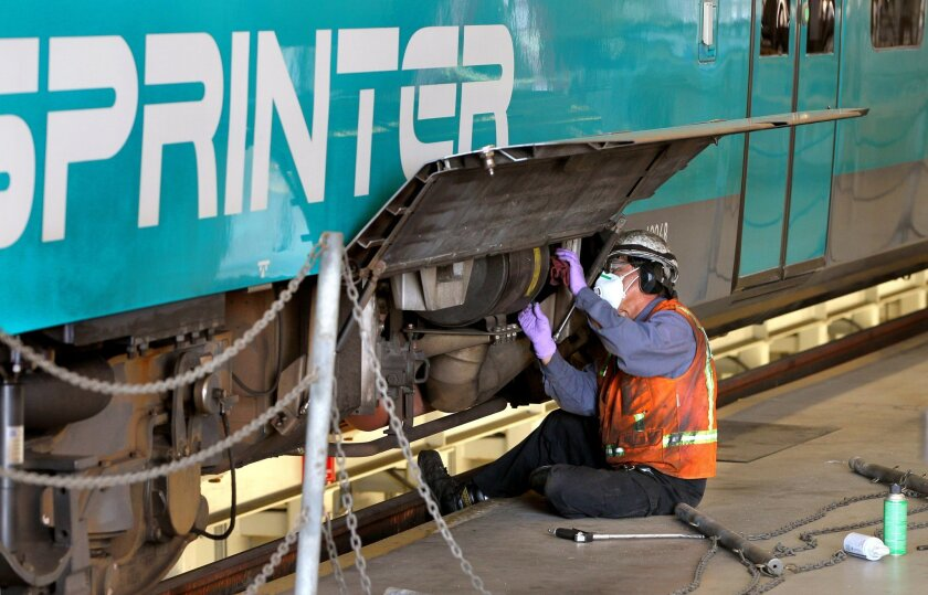 In NCTD's Escondido Sprinter maintenance facility an employee cleans air filters on one of the trains.