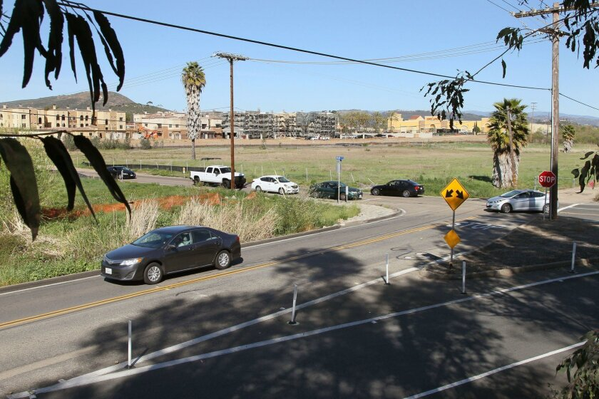 High angle view of the intersection of Discovery Street (foreground) at Bent Avenue, near San Marcos Creek. The area sometimes floods after big storms, and the city is working on a $62 million project to add bridges and shore up the creek. In the distance at left is the Promenade at Creekside devel