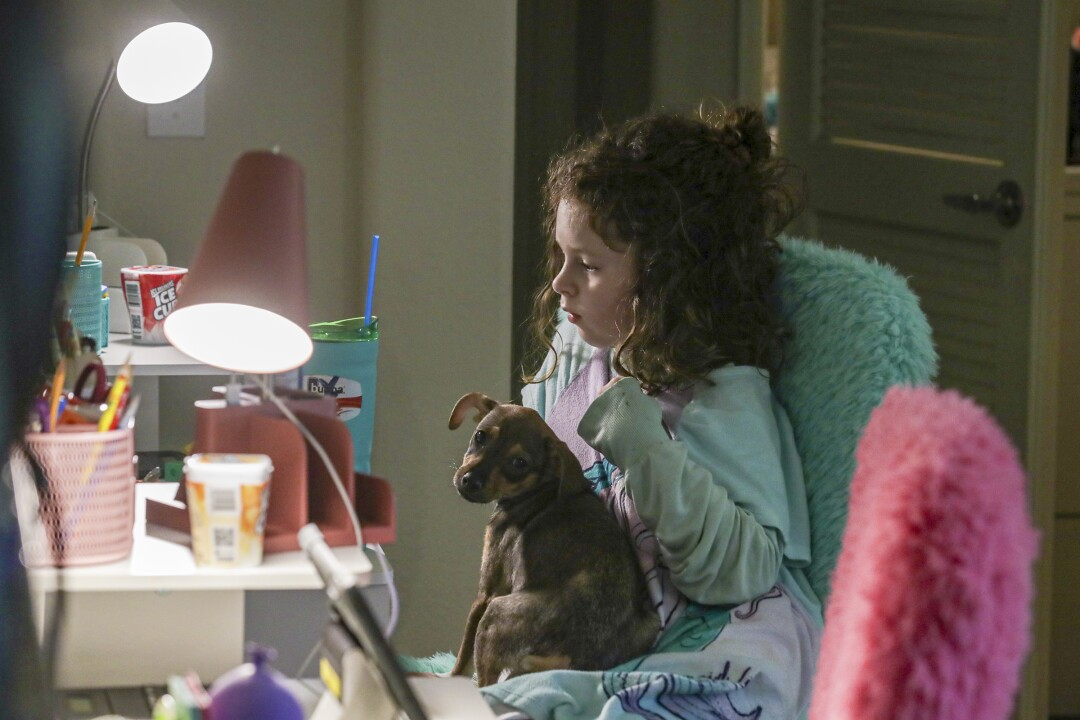 Madelynn Singer, holding support dog Kendall, attends the online school City of Angels at home in Porter Ranch.