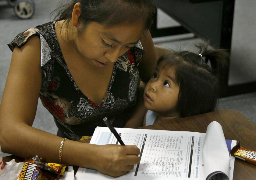 Gabriella Munoz of Orange fills out an application for food stamps while her 2-year-old daughter vies for her attention in October 2006.