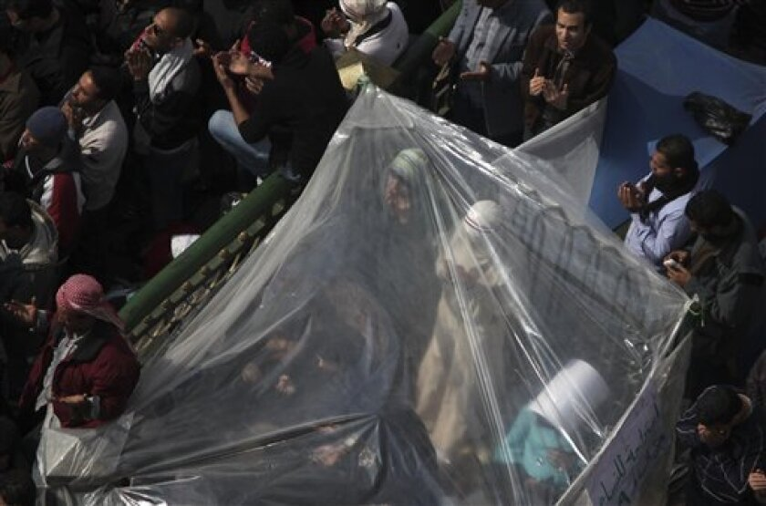 Women anti-government protesters make traditional Muslim Friday prayers inside a makeshift tent at the continuing demonstration in Tahrir Square in downtown Cairo, Egypt Friday, Feb. 11, 2011. (AP Photo/Tara Todras-Whitehill)