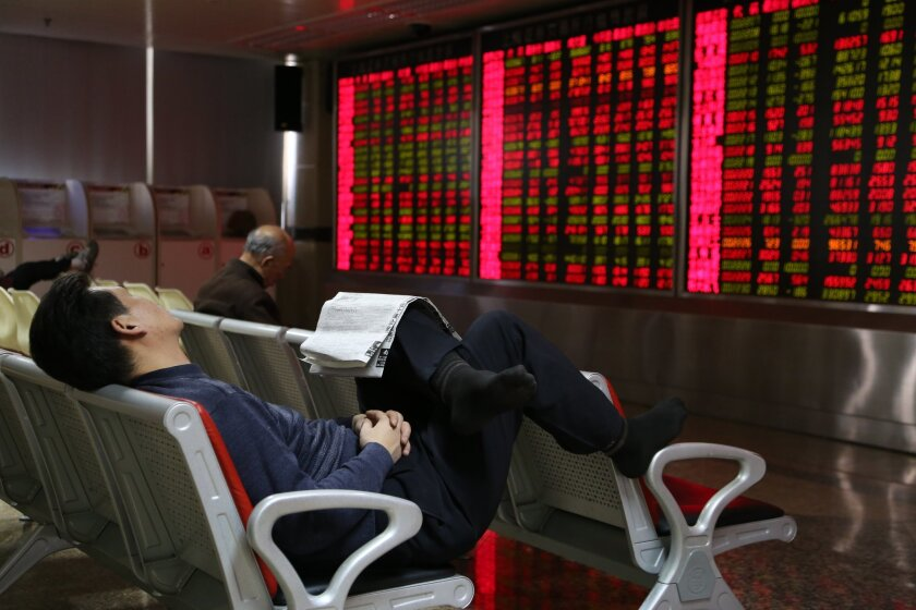 An investor naps while observing stock prices at an exchange hall Friday in Beijing.