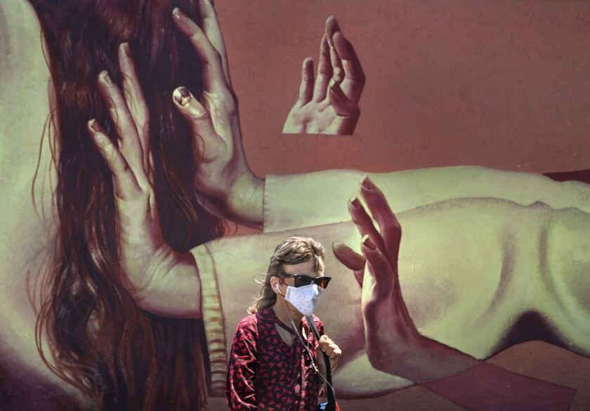 Caroline Kousidonis, 52, of Venice, wears a protective mask while walking past a mural on Lincoln Blvd. in Venice.