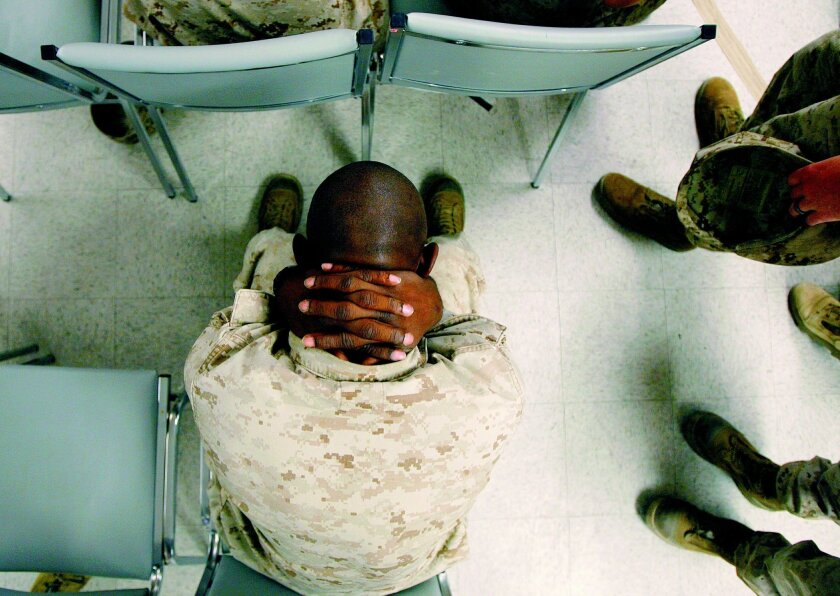 Marine Lance Cpl. Greg Rivers, 20, of Sylvester, Ga., holds his neck while waiting to take psychological tests at the Marine Corps Air Ground Combat Center in Twentynine Palms, Sept. 29, 2007. Jae C. Hong • AP file photos