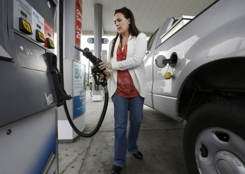 Lydia Holland replaces the gas nozzle after filling up at a gas station in Sacramento, Calif. San Diego, like other parts of the state, have seen reduced gas prices.