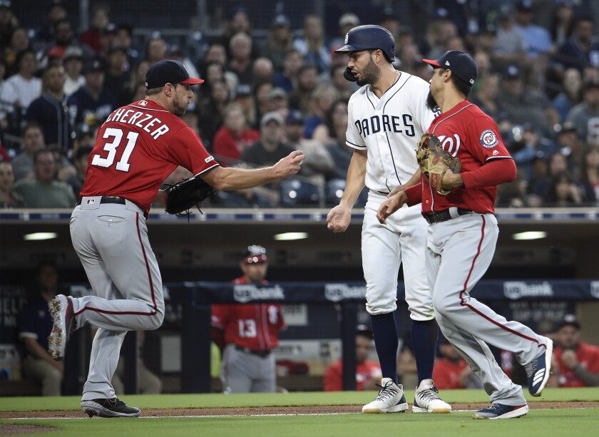 The Padres' Eric Hosmer is tagged out by Nationals pitcher Max Scherzer as Anthony Rendon looks on during the second inning of Saturday night's game at Petco Park.