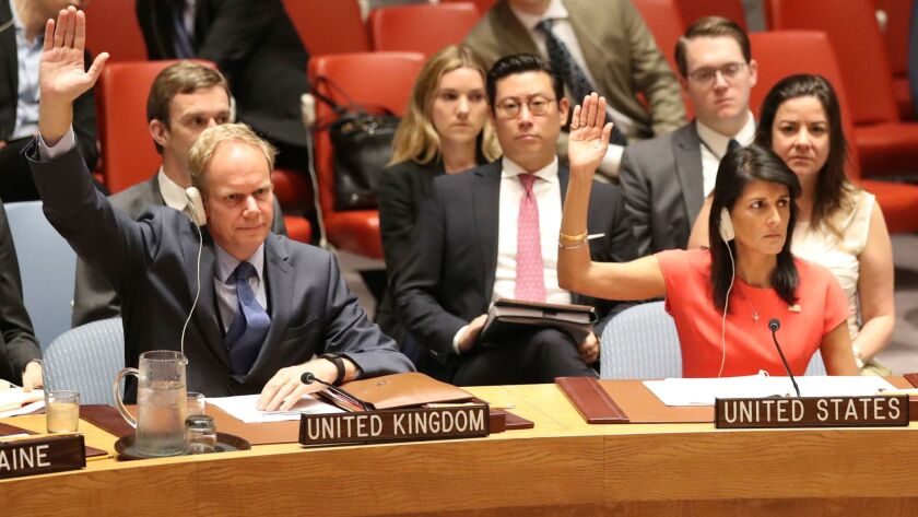 British Ambassador Matthew Rycroft and U.S. Ambassador Nikki Haley vote during a U.N. Security Council meeting on North Korea sanctions on Saturday in New York.