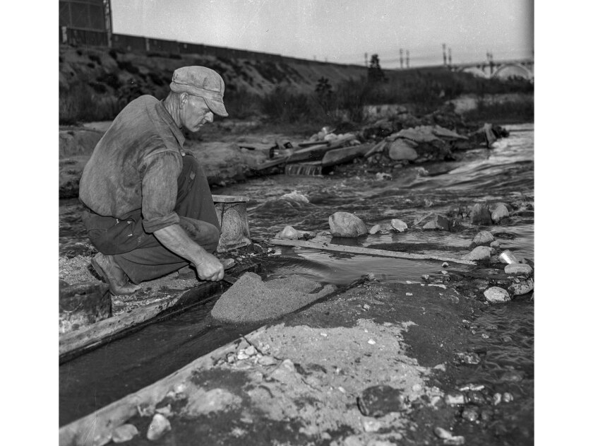Dec. 11, 1938: Guy Ritter examines his painnings from the Los Angeles River. This photo appeared in