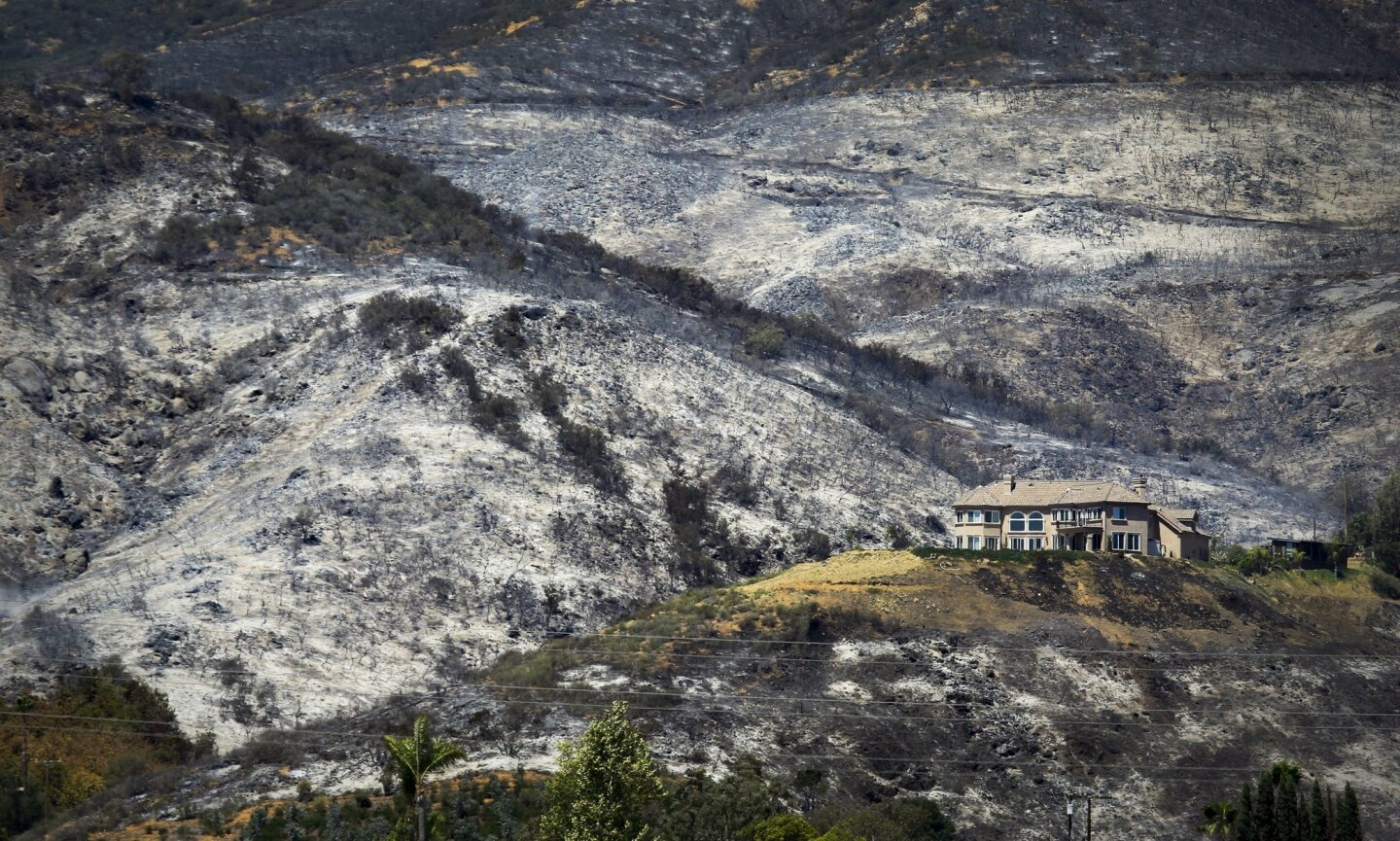 A home saved from the fire is surrounded by a blackened moonscape in the unincorporated area of Escondido.