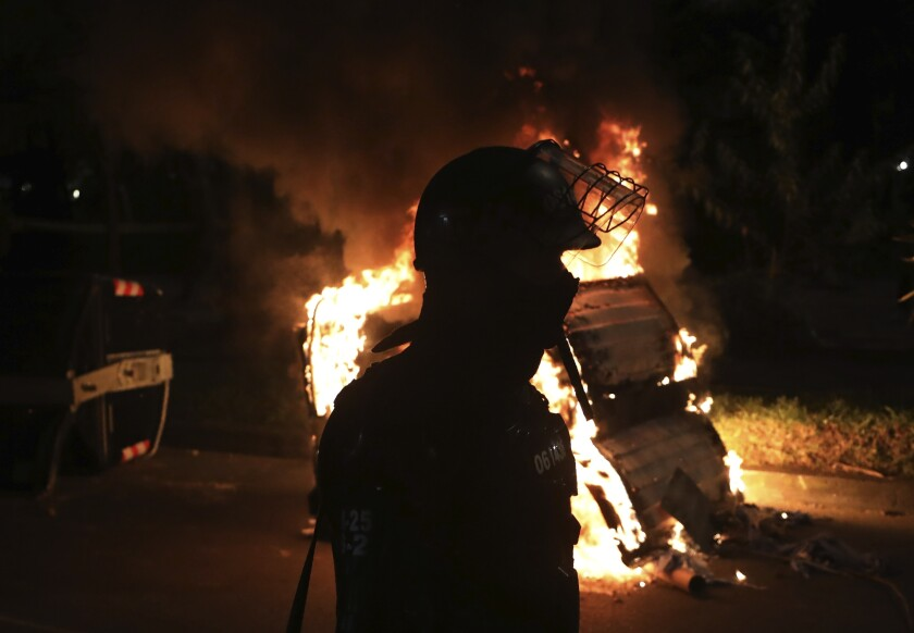 A police officer in riot gear stands behind a burning barricade during protests against the death of a man who was detained by police for violating social distancing rules to curb the spread of the new coronavirus, in Bogota, Colombia, Thursday, Sept. 10, 2020. Javier Ordonez died in a hospital Wednesday after receiving repeated electric shocks with a stun gun from officers who detained him, seen on a video taken by Ordonez's friend, and published on social media. (AP Photo/Fernando Vergara)