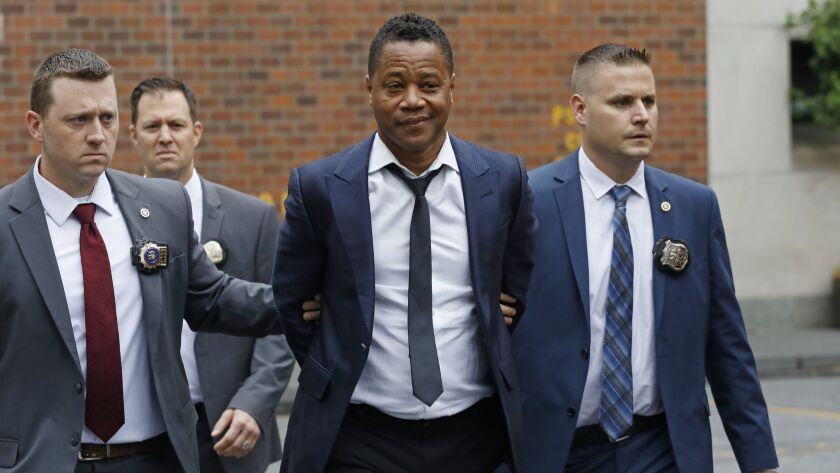 Actor Cuba Gooding Jr., center, is lead by police officers from the New York Police Department's spe