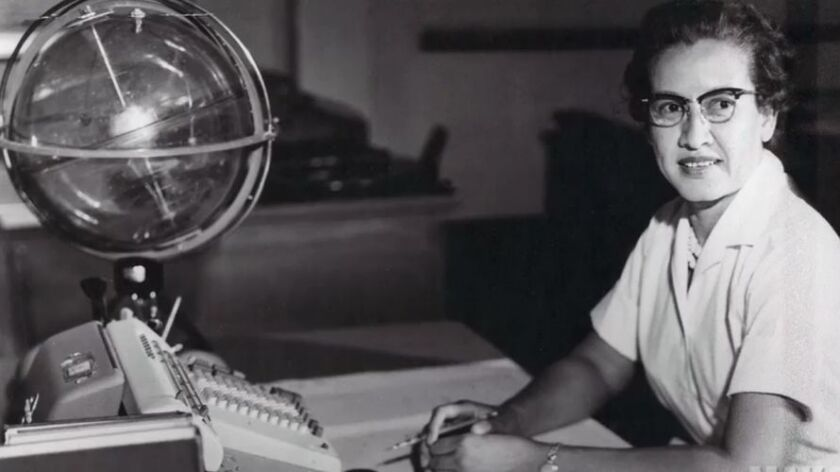 """Katherine Johnson sits at her desk with a globe known as a celestial training device. The lives of Johnson and other black female mathematicians and engineers are featured in the film """"Hidden Figures."""""""