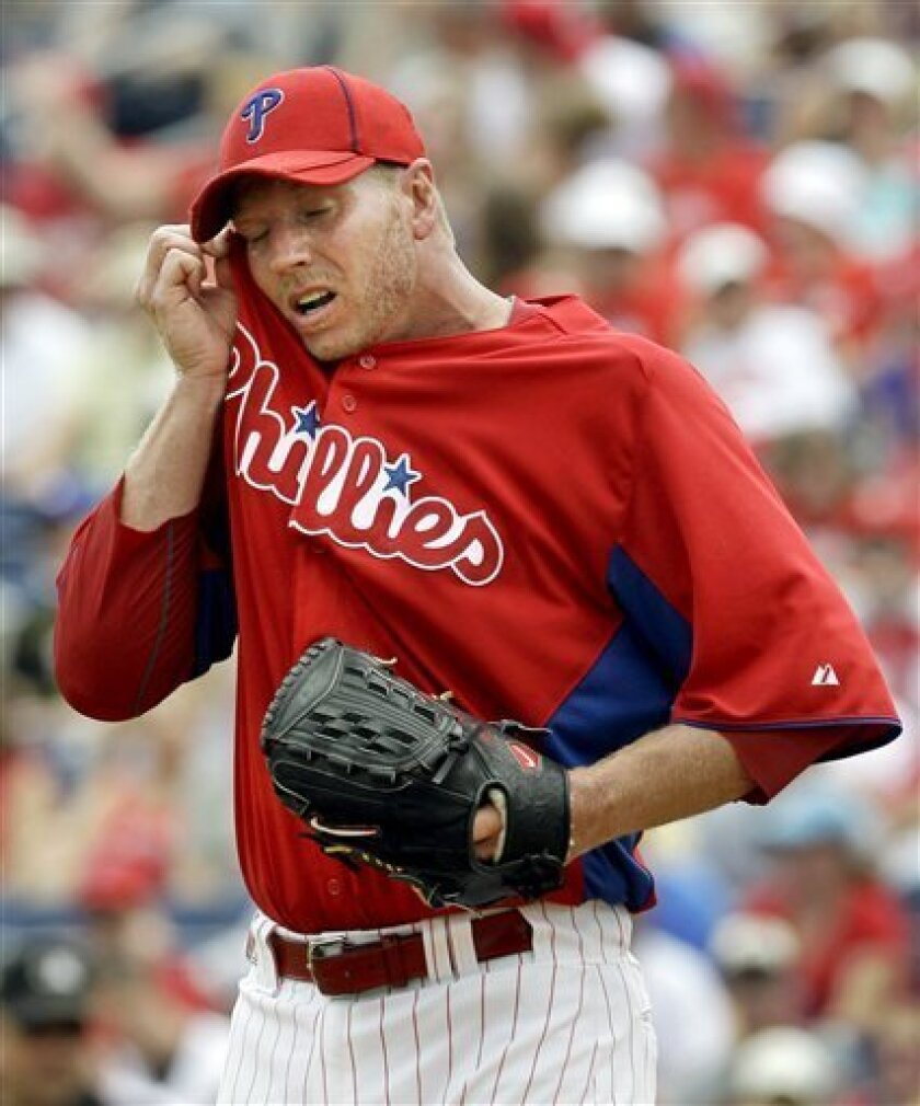 Philadelphia Phillies starting pitcher Roy Halladay wipes his face during the second inning of a spring training baseball game against the Toronto Blue Jays in Clearwater, Fla., Saturday, March 31, 2012. (AP Photo/Kathy Willens)
