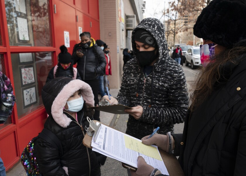FILE - In this Dec. 7, 2020, file photo, a parent, center, completes a form granting permission for random COVID-19 testing for students as he arrives with his daughter, left, at P.S. 134 Henrietta Szold Elementary School, in New York. Children are having their noses swabbed or saliva sampled at school to test for the coronavirus in cities such as Baltimore, New York and Chicago. As more children return to school buildings this spring, widely varying approaches have emerged on how and whether to test students and staff members for the virus. (AP Photo/Mark Lennihan, File)