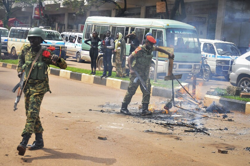 Security forces remove the remains of a burning makeshift roadblock in downtown Kampala on Wednesday.