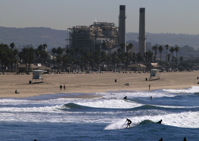 Surfers ride their waves in Huntington Beach while the AES power plant stands in the background in November 2013. Poseidon Water has collected all but one permit to start building its desalination plant next to the AES facility.
