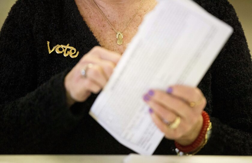 "A ""vote"" pin decorates the sweater of ward clerk Lynn Lavigne as she opens absentee ballots for the New Hampshire primary, Tuesday, Feb. 9, 2016, at a polling place in Manchester, N.H. (AP Photo/David Goldman)"