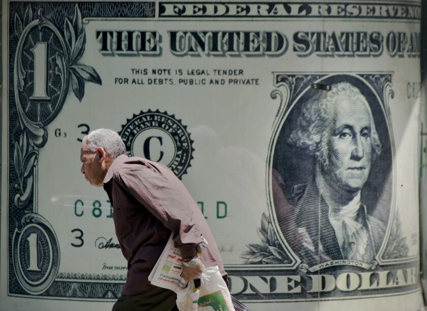 ARCHIVO - Un hombre pasa por delante de un cartel que muestra un dólar estadounidense en las afueras de una oficina de cambio monetario en El Cairo el 17 de agosto del 2016. (AP Foto/Amr Nabil)
